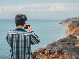 un uomo fa una foto al telefono, in piedi su una roccia
