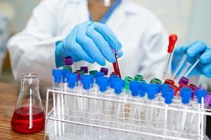 scienziato che tiene e analizza il tubo di micro biologico foto