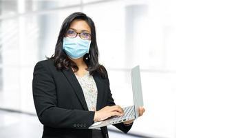 signora asiatica che indossa una maschera in ufficio per proteggere il coronavirus. foto