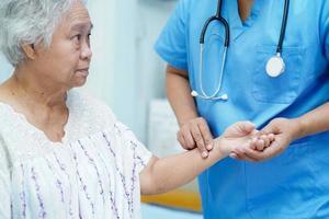medico che controlla paziente asiatico senior della donna in ospedale. foto