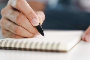 mani del giovane che scrivono sul blocco note, taccuino usando la penna foto