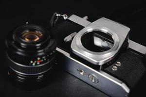slr fotocamera a pellicola e un obiettivo su sfondo nero, concetto di fotografia foto