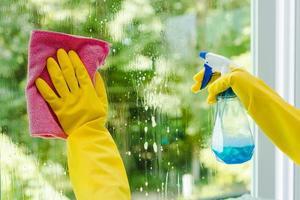 donna che spruzza e pulisce il vetro foto