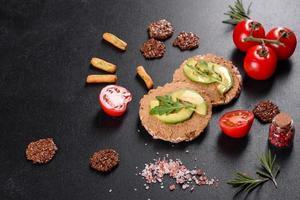 gustoso panino fresco con pasta di fegato, pezzi di avocado e rucola foto