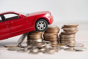 auto sulla pila di monete. prestito auto, finanza, risparmio di denaro foto