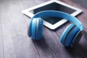concetto di audiolibro. cuffie e tablet digitale sul tavolo foto