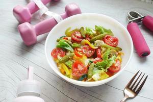 concetto di fitness con manubri, verdura fresca e metro a nastro foto