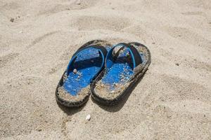 infradito blu sulla spiaggia foto
