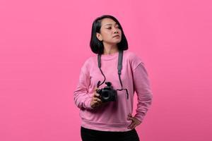 giovane donna che tiene la macchina fotografica con espressione piatta foto