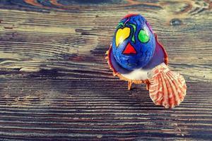 uovo di pasqua colorato su una conchiglia su sfondo di legno foto