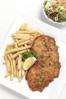 Schnitzel di maiale impanato tedesco con patatine fritte su sfondo bianco per studio foto