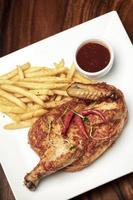 Piri piri portoghese piccante mezzo pollo arrosto con patatine fritte sulla piastra nel ristorante di Lisbona foto