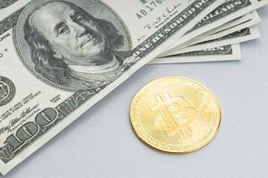 moneta bitcoin e una pila di banconote in dollari americani foto