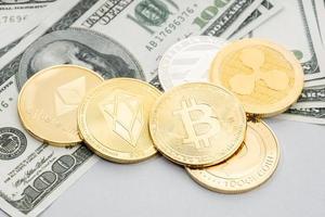gruppo di monete di criptovaluta su sfondo di banconote in dollari foto