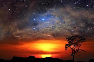 mezzo sole con nuvole rosse sopra la montagna con la nebulosa foto