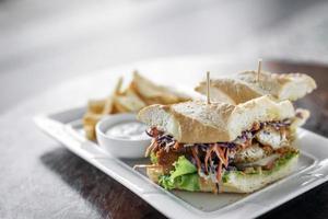 panino di filetto di pesce fresco fritto in pastella con insalata di cavolo cappuccio patatine fritte e salsa tartara foto