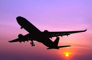 aereo commerciale stagliato che vola al tramonto foto
