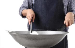 ragazza giovane donna che cucina con padella di ferro su sfondo bianco foto