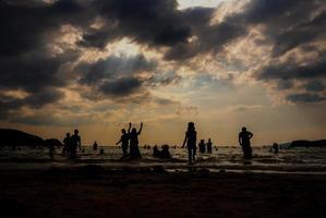 sagome di persone che giocano in mare su una spiaggia pubblica foto
