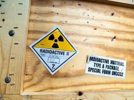 etichetta di avvertenza materiale radioattivo accanto al pacco di trasporto foto