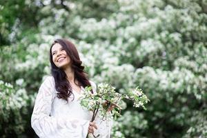 ritratto di una bellissima giovane donna nel parco tra rami fioriti foto