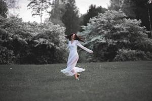 donna felice in abito bianco che balla in un parco cittadino in fiore foto