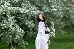 ritratto di giovane donna nel parco tra i rami fioriti foto