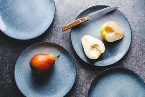 set alimentare in ceramica blu con piatti e pere foto