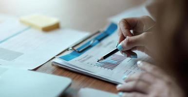 gli uomini d'affari tengono una penna per indicare grafici, grafici, finanza foto
