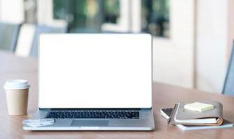 vista ravvicinata del computer portatile con schermo vuoto aperto con ufficio foto