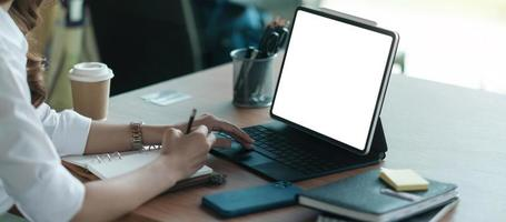 mano ravvicinata di una donna d'affari che digita la tastiera sulla tavoletta digitale foto