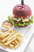 set di snack per hamburger al formaggio con panino rosso di barbabietola con patatine fritte e maionese al peperoncino su piastra bianca foto