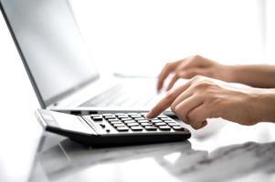mano di donna che usa calcolatrice e laptop foto