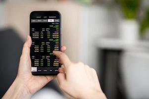 smartphone che tiene in mano il cellulare per il trading online foto
