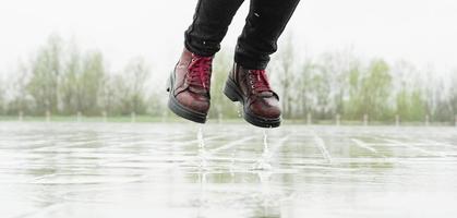donna che gioca sotto la pioggia, salta nelle pozzanghere con schizzi foto