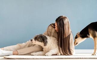 bella donna con cani giocosi che si abbracciano a casa foto