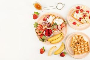 waffle con frutta e bacche, panna e miele in un piatto foto