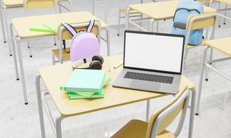 laptop su un banco di scuola in un'aula con libri e forniture in giro foto