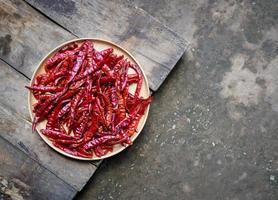 Peperoncini rossi roventi secchi in ciotola di legno sul pavimento di legno foto