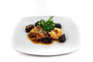 piatto di baccalà in agrodolce su piatto bianco foto
