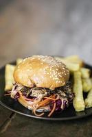 panino con hamburger di maiale stirato e insalata di insalata di cavolo con patatine fritte spuntino foto