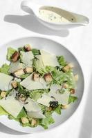 caesar salad con parmigiano e crostini su tavola di legno foto