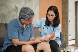 medico terapista femminile esami paziente anziano a casa. foto