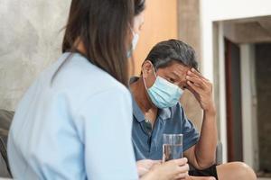 dottore con bicchiere, aiuta il paziente a prendere medicine. foto