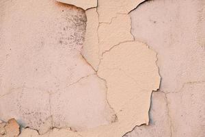 vernice scrostata incrinata sul vecchio muro, primo piano, sfondo foto