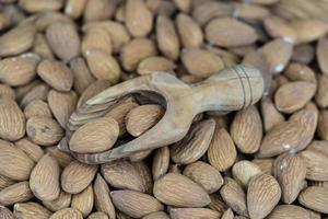 un mucchio di mandorle sgusciate su legno d'ulivo foto