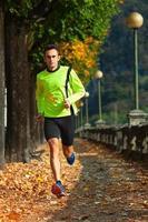 uomo atleta corre in allenamento in autunno foto