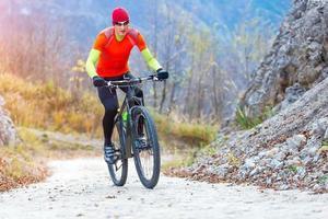 uomo in mountain bike corsa in salita su strada cementata foto