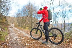 uomo mountain bike riposa e beve dalla mensa foto