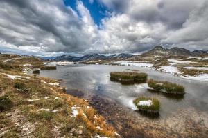accanto a un piccolo lago di montagna foto